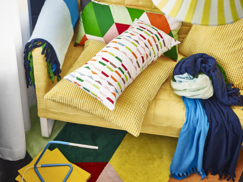 A yellow sofa with multicoloured cushions and throws on a multicoloured rug