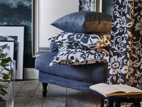 A dark gray armchair with a stack of cushions behind a floral curtain in gray and white