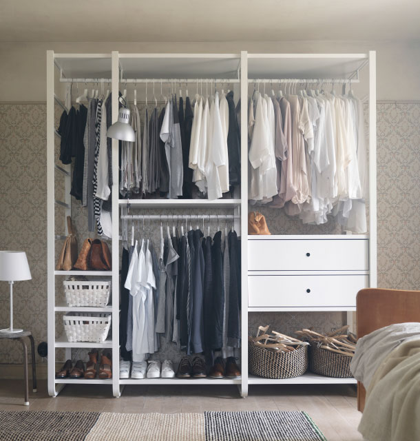 A white open storage with clothes rails, shelves and drawers.