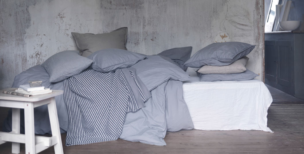 A bed with quilt covers and pillowcases in grey and light blue.