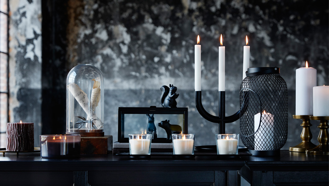 A display of a black candlestick with three lit candles, a glass dome, black decoration animals in the shape of a squirrel, a bear and a rabbit.