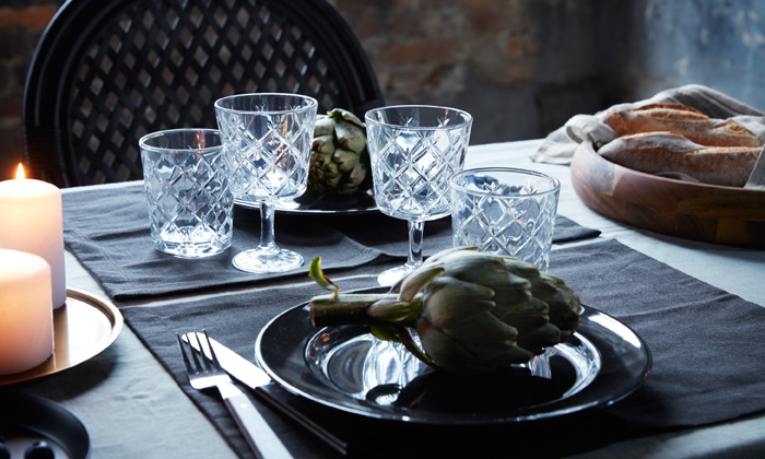 A set table for two with lit candles, wine glasses with cut pattern, black plates and place mats.