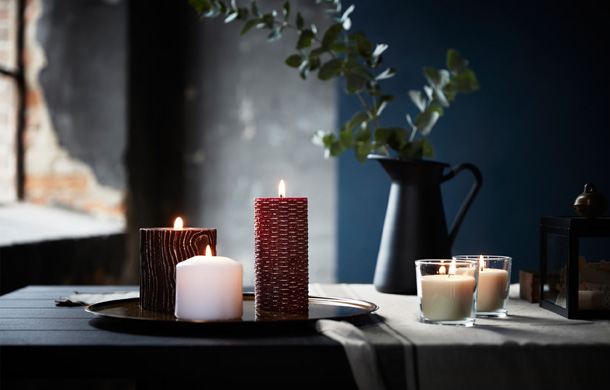 Lit candles in different shapes and sizes, both scented and unscented.