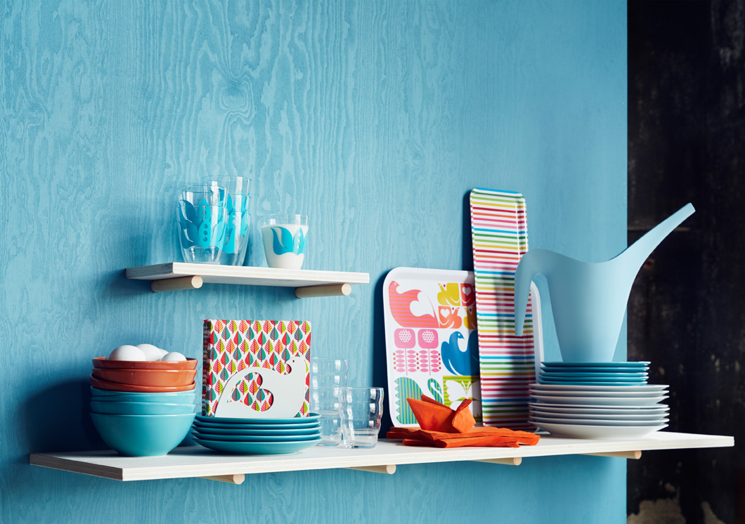 A display of colourful trays, paper napkins, glasses and bowls.