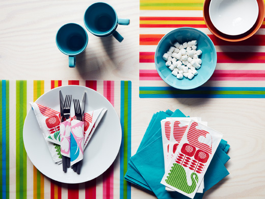 Colourful paper napkins with bird pattern and striped place mats, seen from above.
