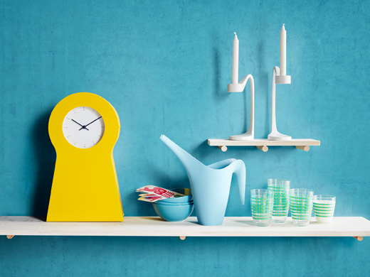 A display of a yellow clock with storage, white candlesticks, a light blue watering can and glasses with a green stripe.