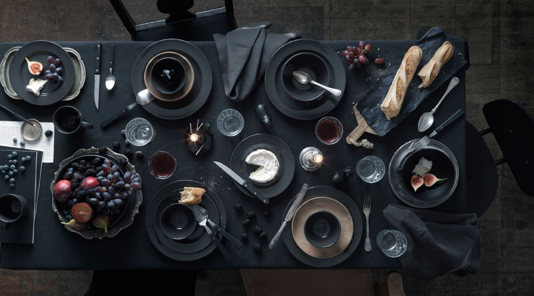 A ready-laid table with bowls and plates in dark grey stoneware.