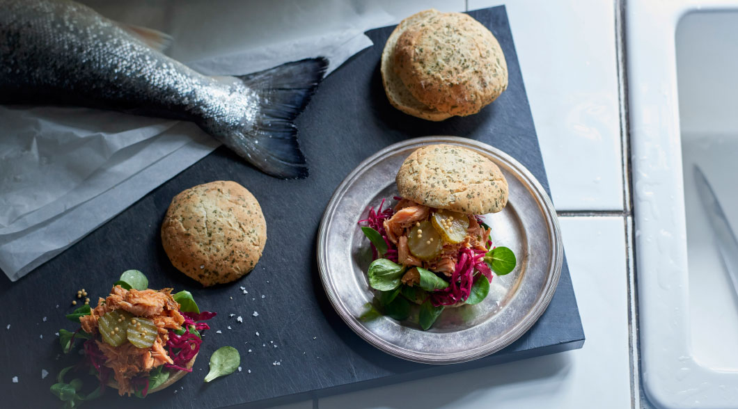 Hot-smoked salmon with a spicy and smoky BBQ kick, served in a wild garlic sourdough bun with green leaf salad, pickled red cabbage and sweet and sour pickled gherkins.