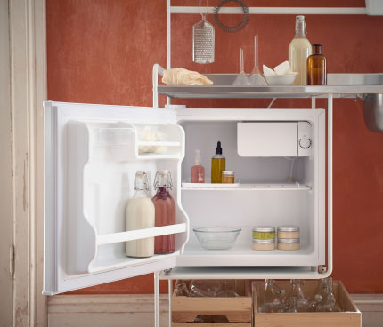 A small fridge filled with bottles and jars, and comes with a small chill compartment.