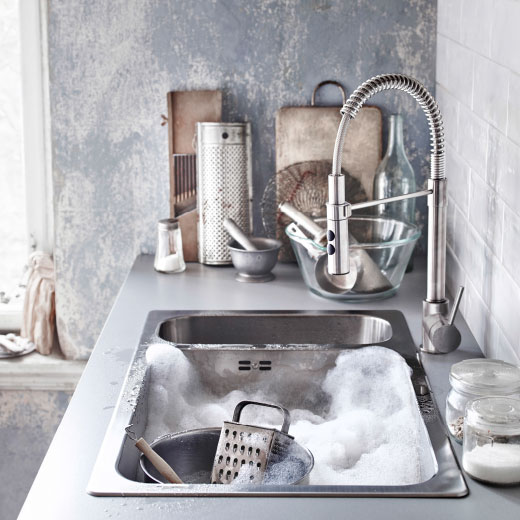 A rectangular stainless steel sink with two bowls, one large and one small, and a kitchen mixer tap with handspray.