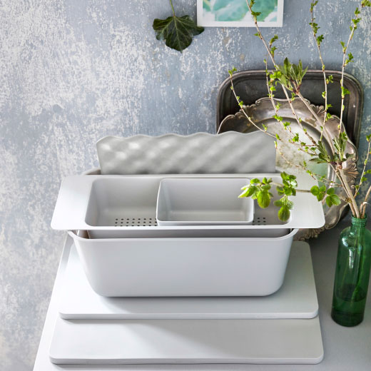 A display of grey sink accessories consisting of a box, colander, washing-up bowl, chopping boards and a mat.
