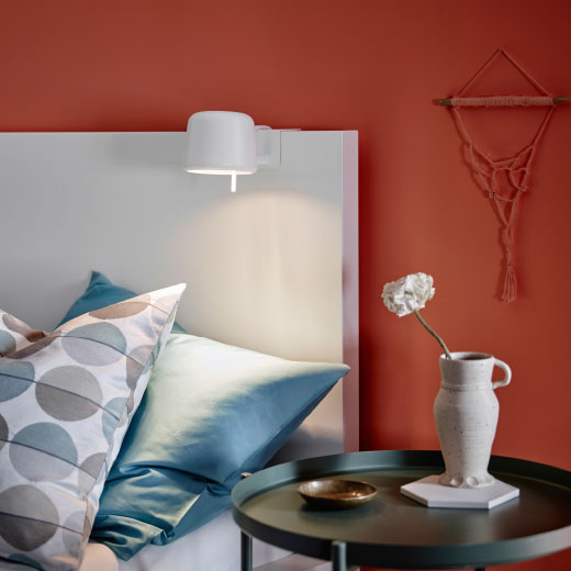 A white clamp spotlight attached to a headboard.
