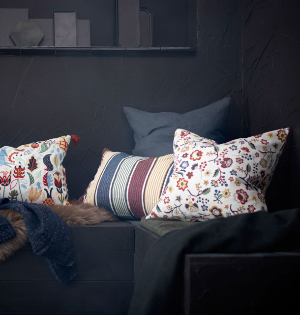 Three different cushions with embroidery, stripes and floral pattern.