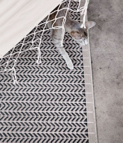 Close-up of a beige rug with a herringbone pattern, that can be used both indoors and outdoors.