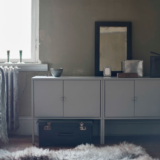 Two grey cabinets on legs used as a sideboard.