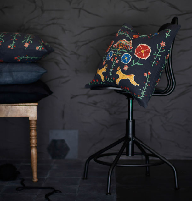 A black cushion with colourful embroidery.