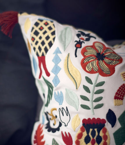 Close-up of a white cushion with colourful embroidery.