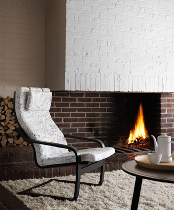 An armchair  in front of an open fire, with layer-glued bent beech frame, stained black-brown, and a white cushion with black leaf pattern.