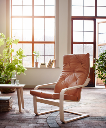 An armchair with layer-glued bent birch frame and a natural-coloured leather cushion.