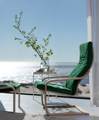 An armchair and footstool with layer-glued bent birch frames and green cushions, with a sunny sea view behind.