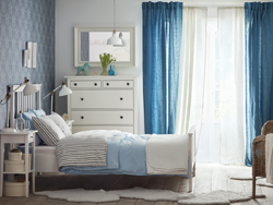 Medium sized room with white double bed and bedding in light blue and gray. A chest of drawers, a mirror and two white bedside tables complete the set.