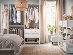 A medium sized bedroom furnished with open floor-to-ceiling storage, consisting of white shelves, clothes rails, drawers and posts.