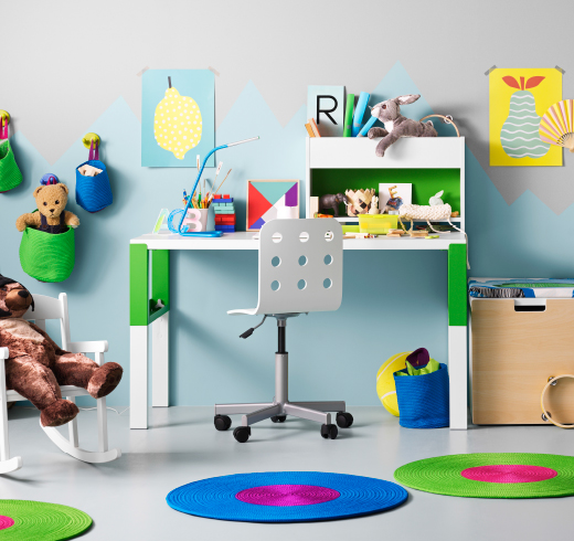 A children's room with a white/green desk that can be adjusted in three different heights as the child grows. Completed with a white/green desk top shelf and a white desk chair.