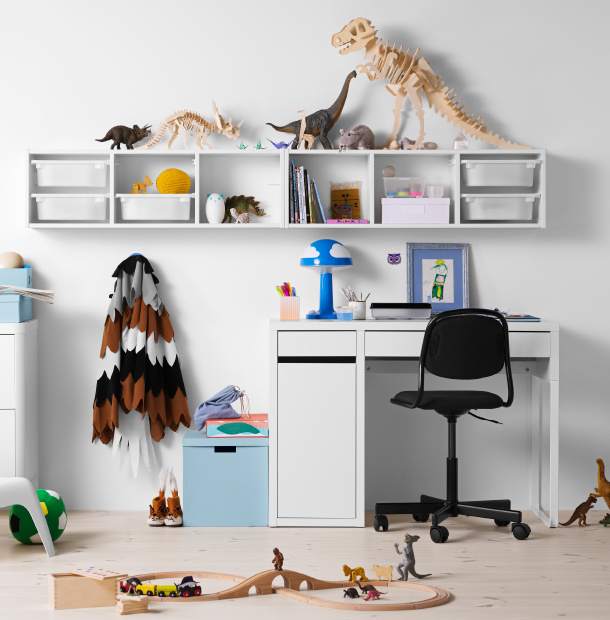 A children's room with a white desk combined with a black swivel chair on castors and a white wall shelf with storage boxes.