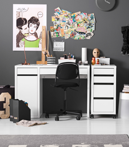 A children's room with a white desk and a drawer unit on castors combined with a black swivel chair on castors.