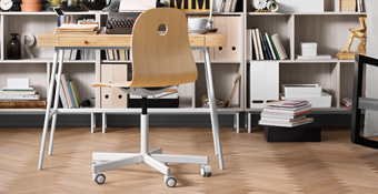 A workroom with a swivel chair on castors in birch/white combined with a desk in bamboo with white legs.