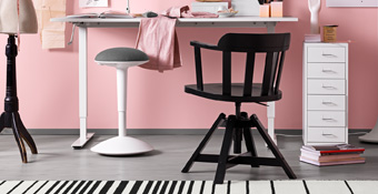 A craft room with a white desk that can be adjusted in height shown together with a black swivel chair with armrests.