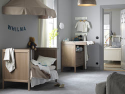 A children's room with a grey-brown cot converted into a children's bed with a beige bed canopy. Shown together with a grey-brown changing table and a wardrobe.