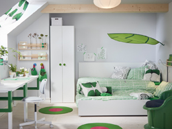 A medium sized children's room furnished with a white bed with an underbed for sleepovers. Shown with bedlinen in green and white and two desks that can be adjusted to three different heights.