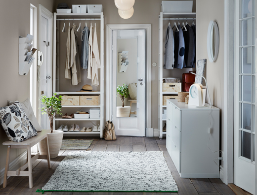 A hallway with floor-to-ceiling storage, consisting of white shelves, clothes rails and posts for storing clothes, bags and shoes. Shown together with two white chest of drawers and a bench in white stained solid birch.