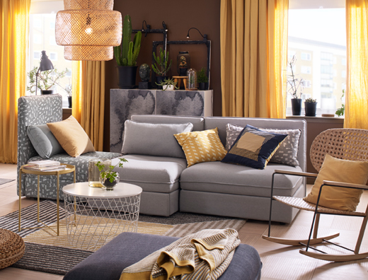 A medium sized livingroom furnished with a three-seat sofa combination in plain grey and with black/beige pattern, that can be converted into a bed. Combined with a white storage table and a modern rocking-chair in handwoven rattan.