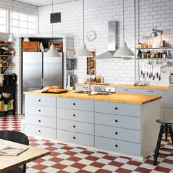 A large kitchen with grey drawers and doors and wooden worktops. Shown together with stainless steel appliances.