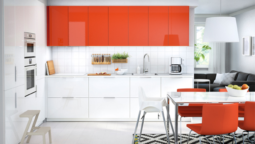 A small kitchen with orange high-gloss wall cabinets and white high-gloss base cabinets. Shown together with stainless steel appliances.