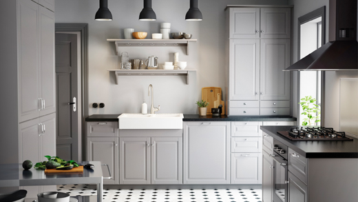 A large kitchen with grey drawers and doors and black worktops. Shown together with black appliances.