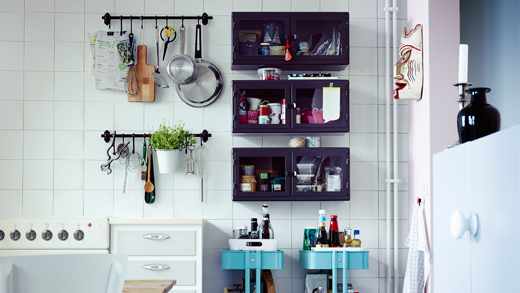 A kitchen wall with black rails filled with kitchen utensils and black glass-door cabinets with groceries.