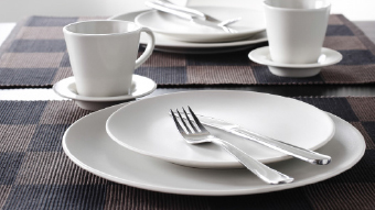 A set table with white stoneware plates, coffee cups with saucers and stainless steel cutlery.