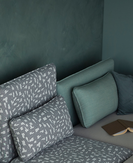 A close-up of sofa combination in green and black/white pattern.
