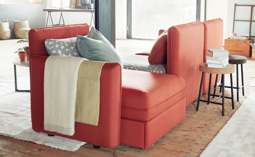 A sofa combination in orange and black/beige, that seats three, consisting of corner modules and a sofa-bed module.
