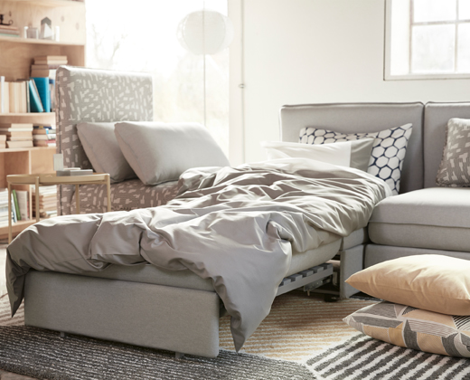 A sofa combination in grey and black/beige consisting of one-seat modules and a sofa-bed module.