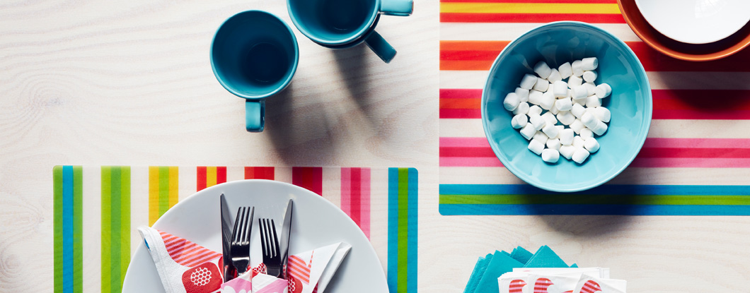 Turquoise stoneware mugs and bowls shown together with colourful striped place mats, seen from above.
