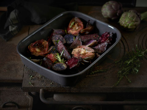 An oval oven dish in dark grey stoneware with roasted vegetables.