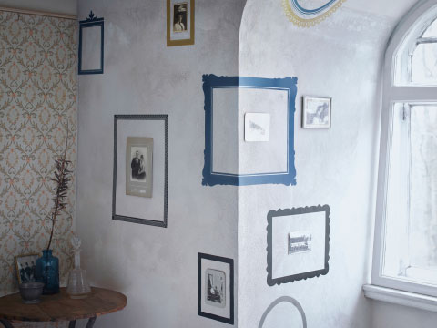 A wall filled with decoration stickers in the shape of different picture frames.