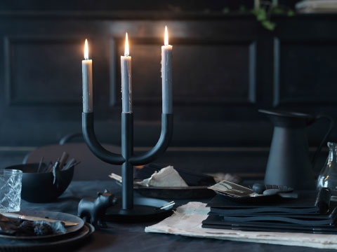 A black three-armed candlestick with lit grey-blue candles.