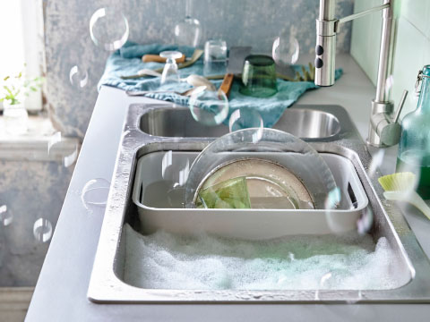 A grey washing-up bowl filled with dishes stands in a stainless steel sink.