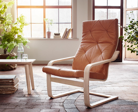An armchair with layer-glued bent birch frame and a natural-colored leather cushion.