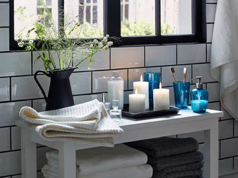 A white bench with lit block candles, turquoise soap dispenser and toothbrush mug, shown in a bathroom.